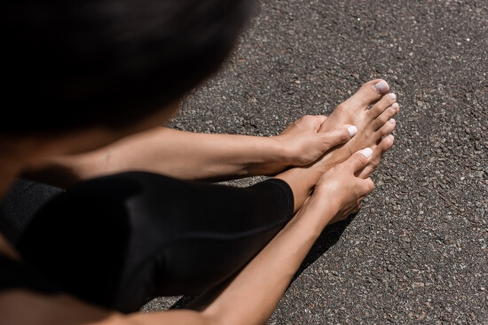 how to wrap foot for top of foot pain - woman holding her foot