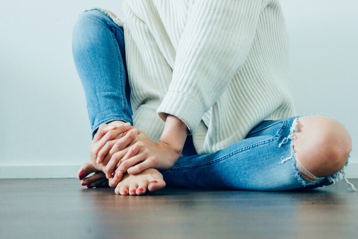 Running Shoes For Sesamoid Pain - woman holding her foot