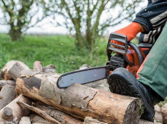 why do logger boots have a heel - man cutting wood with a chainsaw